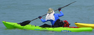 Kayaker with clothing to protect from sun